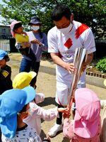 園児にトーチを見せる棚橋さん=阿南市柳島町の中野島保育所