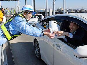 チョコレートなどを手渡し、安全運転を呼び掛ける西日本高速道路の女性職員=午前、徳島市川内町の徳島IC料金所