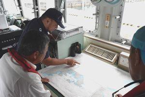海保職員(奥)から海岸線の地形の説明を受ける防災ウオッチャー=牟岐漁港