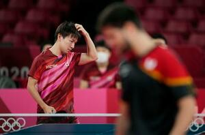 男子団体準決勝 ドイツ戦の第5試合でポイントを奪われ、頭に手をやる丹羽孝希=東京体育館