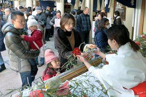宵えびすで福ザサを買い求める参拝客=徳島市通町2の事代主神社