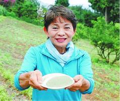 栽培地の畑で藍の粉を持つ栃谷代表=つるぎ町貞光