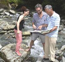 青石の採石地を訪れ、森下さん(右端)に話を聞くロマニさん(中央)とサクリストさん=神山町阿野の広石渓谷