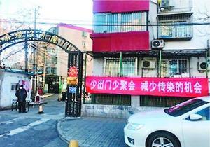 小区の入り口に掲げられたスローガンには「出歩かず集まらず、感染の機会を減らそう!」と書かれていた=北京