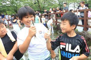 捕まえたアユを見せ合って喜ぶ子どもたち=吉野川市の江川・鴨島公園