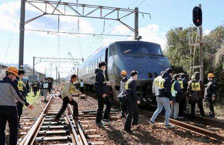 緊急停車した訓練用の特急列車から脱出する乗客ら=17日午後、宮崎県日向市