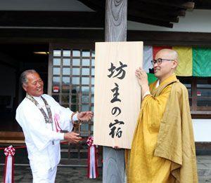 シームレス民泊の開業に合わせ、看板を取り付ける谷口副住職(右)=阿南市新野町の平等寺