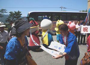 第1便の乗客に記念品を手渡す泉市長(右)=鳴門市のルネッサンスリゾートナルト