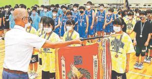優勝旗を受け取る女子・撫養の外川穂華さん=松茂町総合体育館