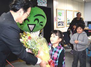 黒石局長(左端)から花束を受け取る山北優衣ちゃん=那賀町吉野の川口ダム自然エネルギーミュージアム