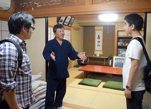 徳島文理大生に宿泊する部屋を紹介するシームレス民泊推進協会の会員(中)=阿南市新野町