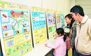 学校給食の取り組み紹介に見入る親子=松茂町広島の町保健相談センター