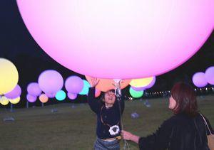 浮遊する球体に触れ、色の変化を楽しむ子どもら=那賀町小仁宇の大塚製薬徳島ワジキ工場野外ステージ