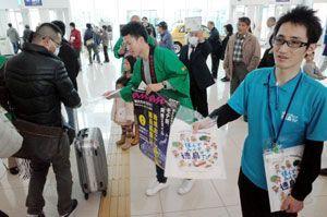 帰省ラッシュに合わせ、徳島への移住を呼び掛ける県職員ら=徳島阿波おどり空港