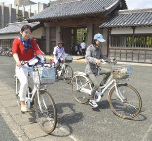 電動アシスト付き自転車でサイクリングを楽しむ「ぐるとくサイクル」ツアーの参加者=徳島中央公園の鷲の門前
