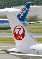 成田空港ですれ違う日本航空機(手前)と全日本空輸機の尾翼