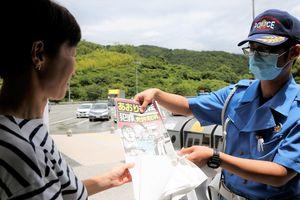 あおり運転厳罰化のチラシを配る県警高速隊員=徳島自動車道の上板SA
