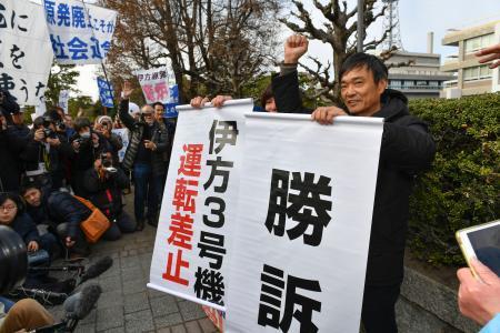 広島高裁が四国電力伊方原発3号機の運転を差し止める仮処分を決定し、垂れ幕を掲げ喜ぶ住民側関係者=17日午後2時3分