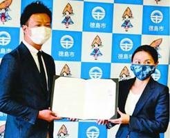 協定書を交わす近藤社長(左)と内藤市長=徳島市役所