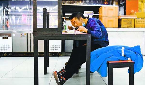 北京市内のフードコートで昼食を取る市民。新型コロナウイルス対策で、テーブルに客が向かい合わせで座らないように片側の椅子が机の上に置かれていた=3月25日(共同)