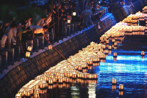 ゆっくりと流れる灯籠を見送る人たち=16日午後7時すぎ、徳島市の新町川