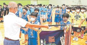 優勝旗を受け取る男子・富岡の射場暖君=松茂町総合体育館