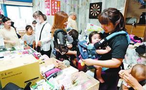フリーマーケットで古着やおもちゃを手に取る買い物客=阿南市の地域交流施設Replay