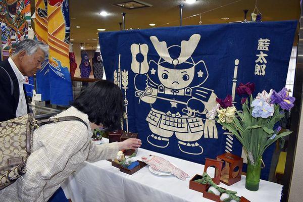 端午の節句にまつわる藍染作品などを見る来場者=徳島市立木工会館