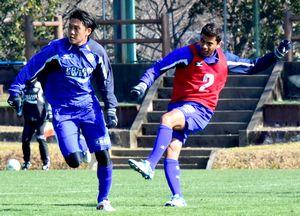 ゲーム形式の練習で激しく競り合う岩尾(左)とカルリーニョス=高知市の春野総合運動公園球技場