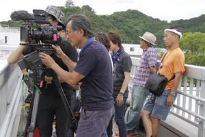 日和佐駅に入る列車を撮影する赤川さん(手前)ら=美波町奥河内の同駅