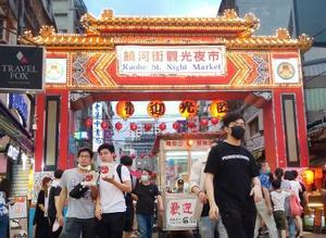 マスク姿の入場者が行き来する台北市内の夜市=5月(AP=共同)