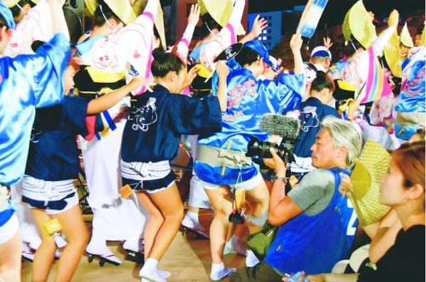 ゑびす連の踊りを撮影する亭田さん(前列右から2番目)=徳島市の新町橋東おどり広場