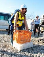 アシストスーツを着用し、荷物を持ち上げる学生=阿波市阿波町王地南