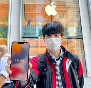 購入したスマートフォン「iPhone(アイフォーン)」の「13」シリーズの新機種を手にする男性=24日午前、東京都内
