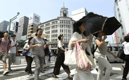 昨夏の猛暑の中、東京・銀座で日傘を差して歩く人たち=2018年7月18日