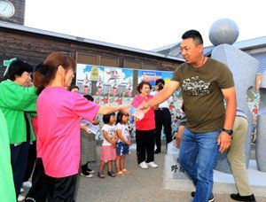 飲み物を手渡して中国のプロ野球チームの選手をもてなす住民ら=阿南市那賀川町
