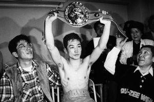 WBC世界ジュニアバンタム級王者となり、試合後の控室でチャンピオンベルトを高々と掲げる川島氏=1994年5月4日、横浜文化体育館