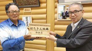 大川村の和田村長(右)から土佐はちきん地鶏取扱店の認定板を受け取る中村理事長=同村役場(新町川を守る会提供)