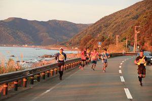 朝日を浴びながら海岸線を走るランナー=2019年4月28日、高知県室戸市