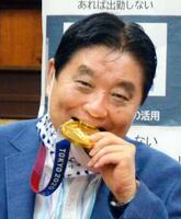表敬訪問を受けた東京五輪ソフトボール日本代表後藤希友選手の金メダルをかじる河村たかし名古屋市長=4日、同市役所