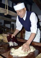 白下糖の結晶を細かくし、糖蜜を抜く「研ぎ」の作業に当たる坂東さん=上板町泉谷の岡田製糖所