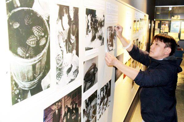 訪問に合わせ、日和佐中の活動などを紹介する写真を展示する日和佐うみがめ博物館カレッタの職員=美波町日和佐浦の同館
