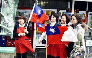 台湾の旗を振って観光客(右端)を見送る従業員。外国人誘致の取り組みが評価された=2015年1月、三好市山城町西宇の大歩危峡まんなか
