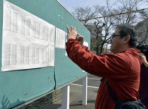 長男が徳島大に合格し、顔をほころばせながら記念写真を撮る父親=徳島大常三島キャンパス