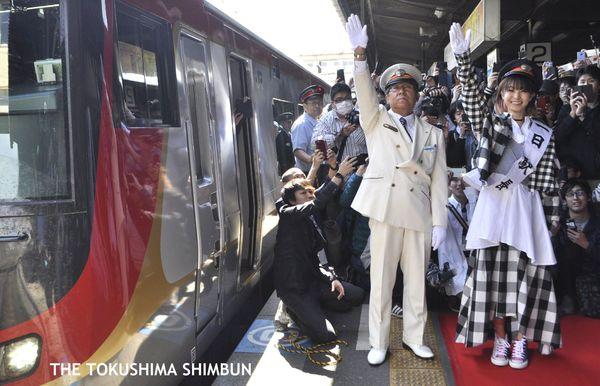 一日駅長として特急列車に発車の合図を送るLiSAさん㊨=JR徳島駅