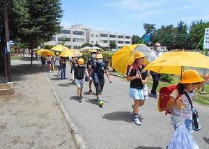 熱中症対策と新型コロナウイルス感染予防のため、晴れの日も傘を差して登下校する埼玉県熊谷市内の小学生=6月(市教育委員会提供)