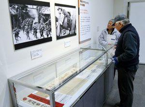 兵士らの苦労を伝える展示品に見入る来場者=県立21世紀館